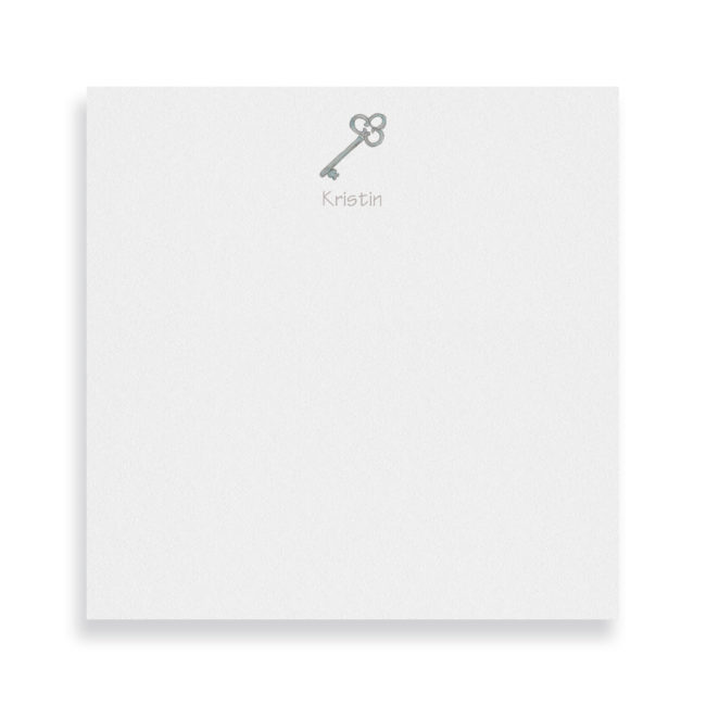 key image adorns a square notepad printed on white paper.