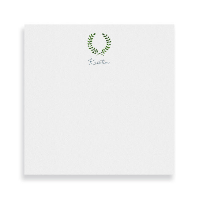 laurel wreath image adorns a square notepad printed on white paper.