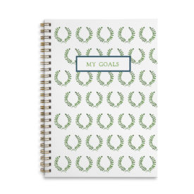 laurel wreath image adorns a spiral bound notebook with blank pages.