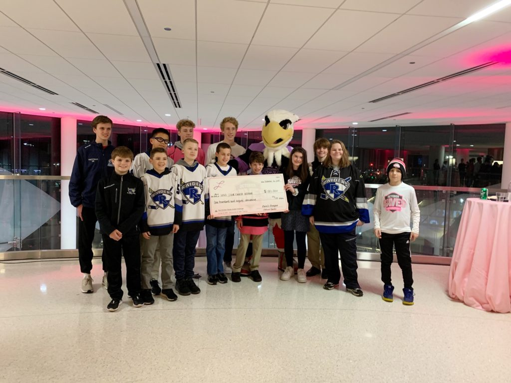 Reston Raiders Hockey Team presenting check to INOVA Schar Cancer Institute